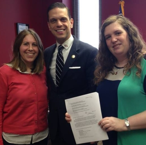 Left to right: Rebecca Botta-Zalucki, Assemblyman Santabarbara, and Henny Kupferstein, holding the signed proposal.