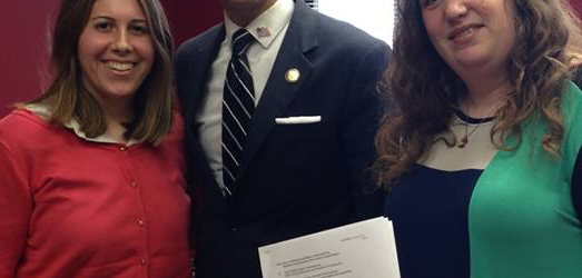 Left to right: Rebecca Botta-Zalucki, Assemblyman Santabarbara, and Henny Kupferstein, holding the signed proposal.